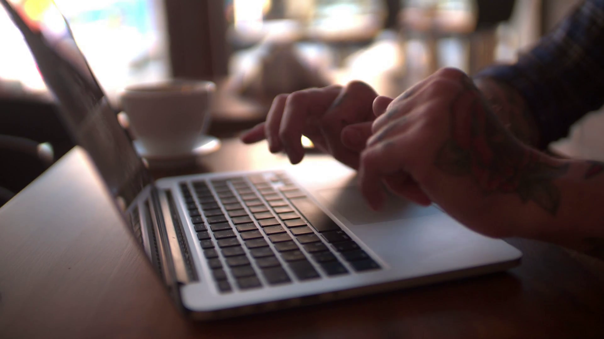 videoblocks-hipster-with-tattoos-at-coffee-shop-typing-on-laptop-keyboard_bue5ffm2l_thumbnail-full01
